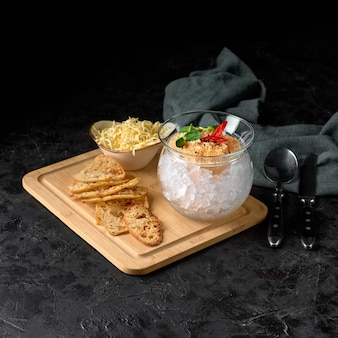 Kawior ze szczupaka, na lodzie, z grzankami i masłem, na przezroczystym naczyniu, na ciemnym tle