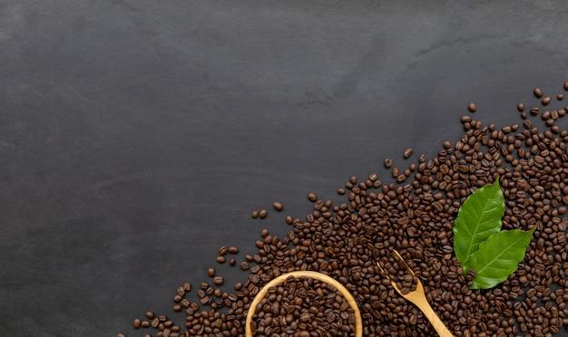 Kawowa fasola na czarnym drewnianym podłogowym tle