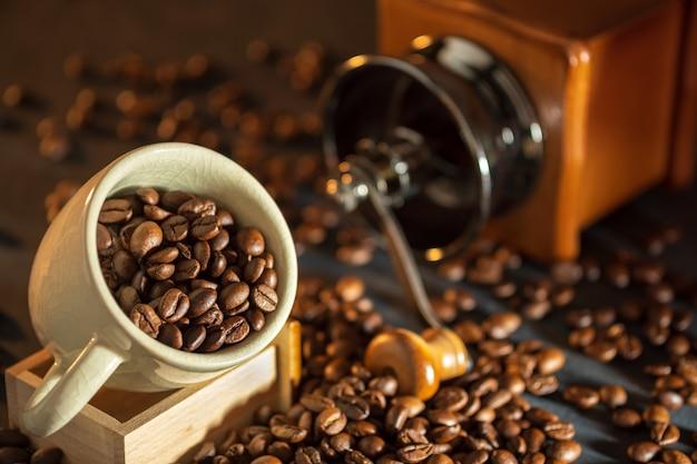 Kawowa fasola w białej filiżance i kawowym ostrzarzu na drewnianym stole. pojęcie śniadania lub poranka kawy rano.