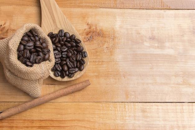 Kawowa fasola w worku i drewnianej łyżce z cynamonem. widok z góry