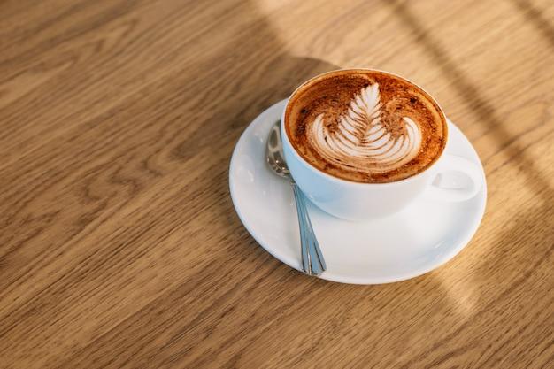 Kawowa latte sztuka na drewnianym stole
