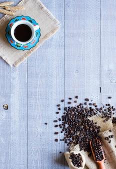 Kawowe fasole i filiżanka kawy z innymi składnikami na różnym drewnianym tle. wolne miejsce na tekst