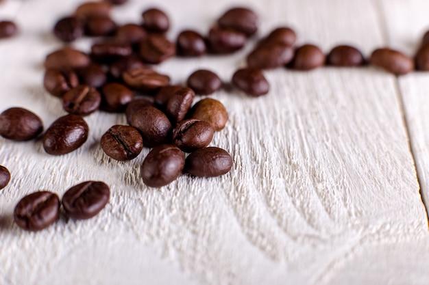 Kawowe fasole lub adra na biały drewnianym. leżał płasko.