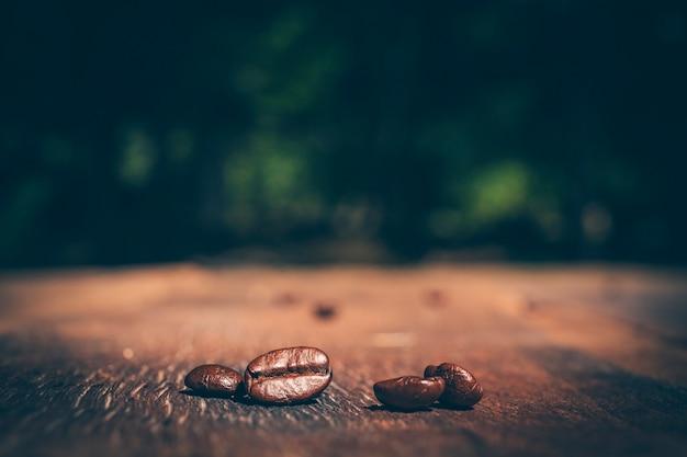 Kawowe fasole na drewnianej teksturze. zbliżenie