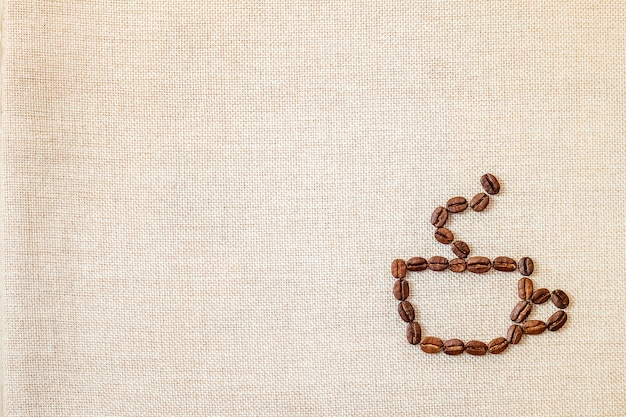 Kawowe fasole na sukiennym tle.