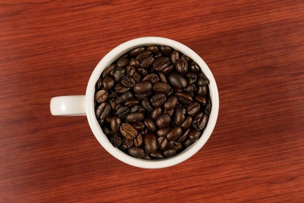 Kawowe fasole w białej filiżance z drewnianym tłem