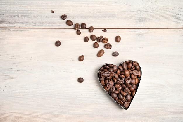 Kawowe serce na jasnym tle. latające serce z ogonem porozrzucanych ziaren