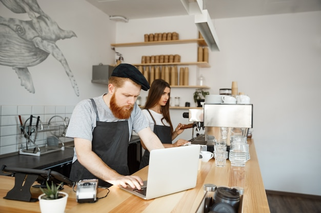 Kawowy biznesowy pojęcie - młody przystojny brodaty barman, barista lub kierownik pracuje i hebluje w laptopie przy nowożytną sklep z kawą.