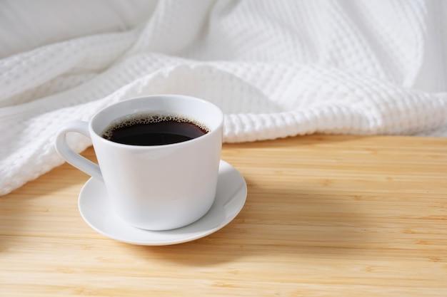Kawowy chlebek w białej filiżance postawionej na łóżku, rano biała pościel, świeże powietrze