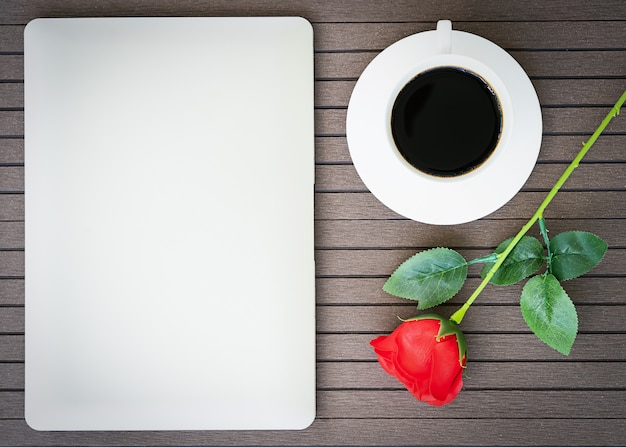 Kawowy czas z laptopem, filiżanką kawy, czerwieni róża