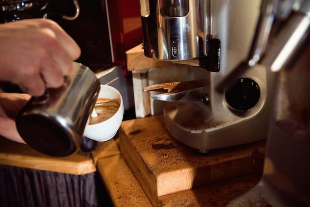 Kawowy latte barista robi wzorowi w filiżance sklep z kawą.