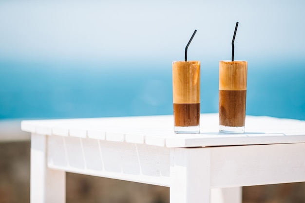 Kawowy latte na drewnianym stole z dennym tłem