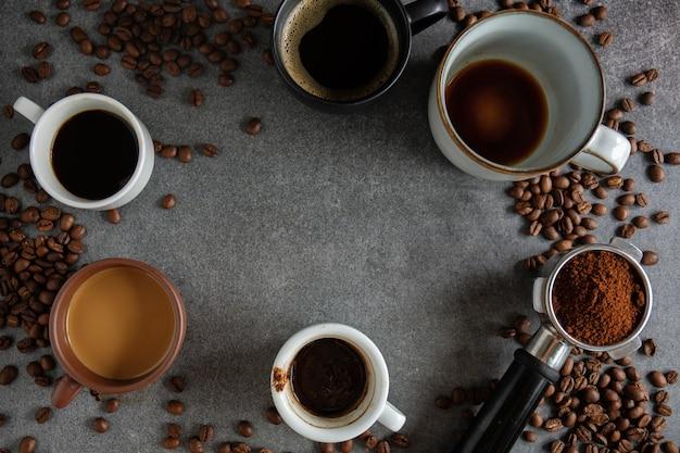 Kawowy tło z kawowymi fasolami, kawą i łyżką na ciemnym tle. widok z góry. koncepcja kawy.