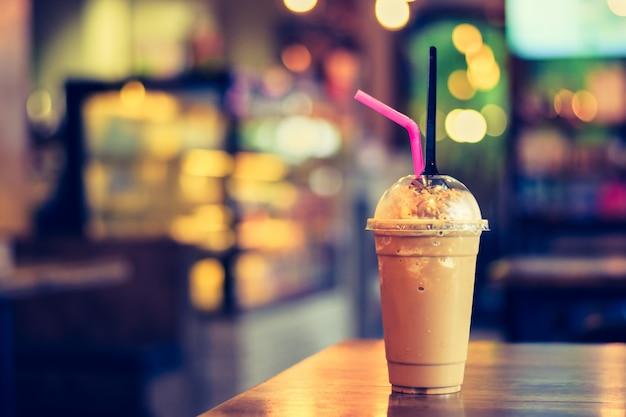 Kawy lub kakao freppe na drewnianym stole z zamazanym tłem w sklep z kawą
