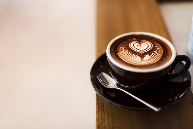 Kawy piana spienia się sztuka na drewnianym stole