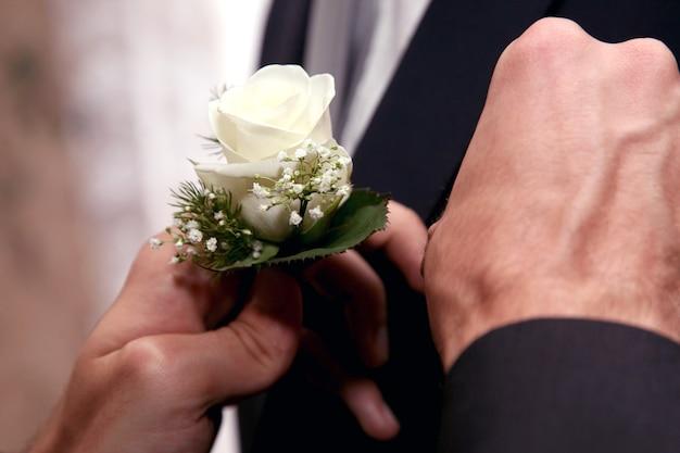 Każdy pomaga ubrać kwiat ślubny na garnitur pana młodego. akcesoria wakacyjne