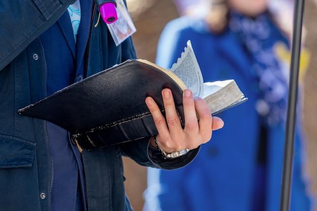 Kaznodzieja z mikrofonem w ręku trzyma biblię i czyta z niej fragment