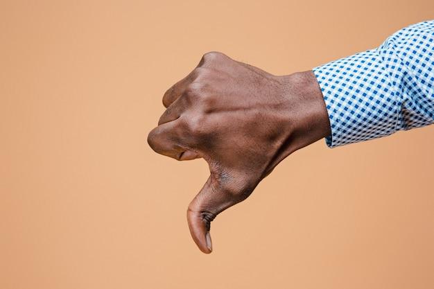 Kciuk w dół znak ręką na brązowy