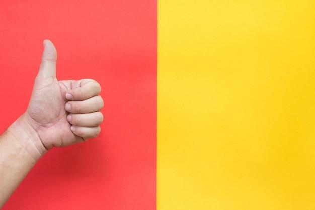 Kciuk w górę na czerwonym i żółtym tle.