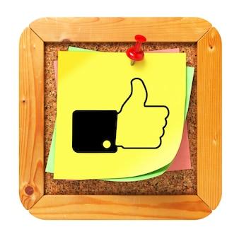 Kciuk w górę na żółtej naklejce na tablicy ogłoszeń korka.