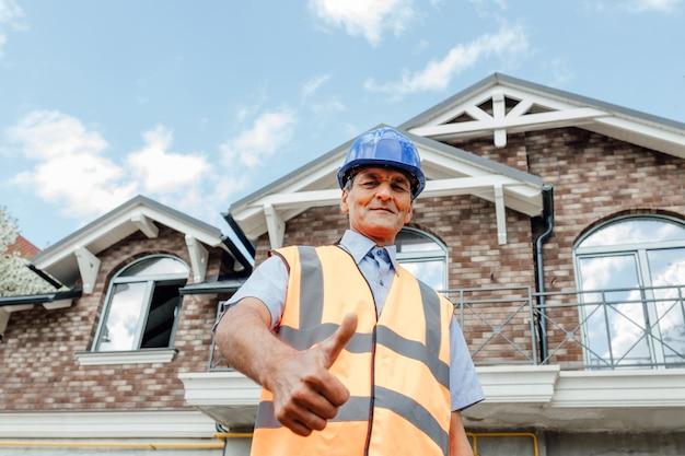 Kciuk w górę od pewnego siebie profesjonalnego azjatyckiego inżyniera płci męskiej budowniczy budowlany architekt pracownik inspektor inwestorski lub architekt pokazujący kciuk w górę inżynierowie budowlani na miejscu