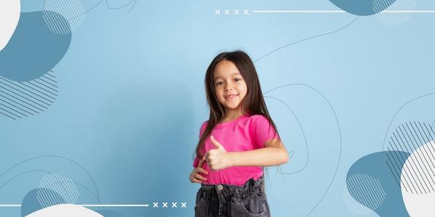 Kciuk w górę, uśmiechnięty. portret dziewczynki kaukaski. piękna modelka na co dzień. pojęcie ludzkich emocji, wyraz twarzy, sprzedaż, reklama, miejsce. jasne, nowoczesne tło ilustrowane.