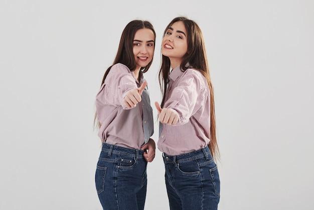 Kciuki w górę. dwie siostry bliźniaczki stojąc i pozując