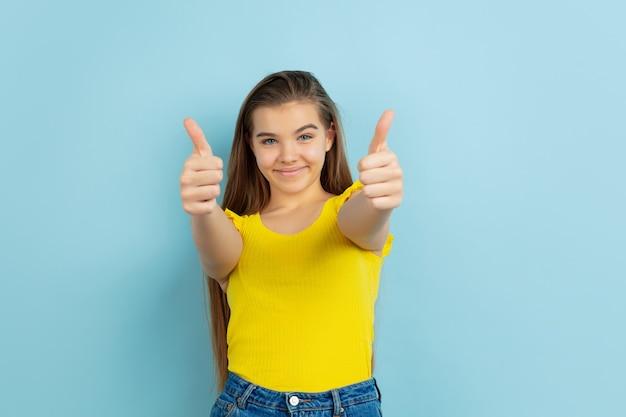 Kciuki w górę. portret kaukaski teen girl na białym tle na niebieskiej ścianie. piękny model w swobodnym żółtym kolorze. pojęcie ludzkich emocji, wyraz twarzy, sprzedaż, reklama. copyspace. wyglądać słodko.