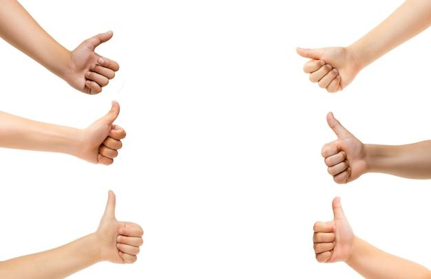 Kciuki w górę. ręce dzieci gestem na białym tle na tle białego studia, miejsce dla reklamy. tłum dzieci gestykuluje. pojęcie czasu dzieciństwa, edukacji, przedszkola i szkoły. znaki i zmysły.