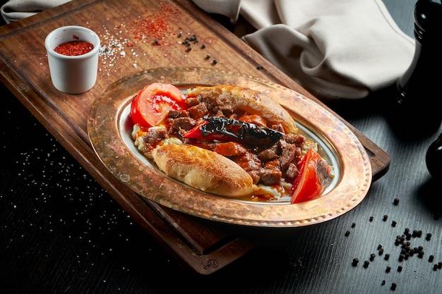 Kebab alinazik to danie z grillowanego bakłażana i jagnięciny w bułce na miedzianym talerzu. czarny stół