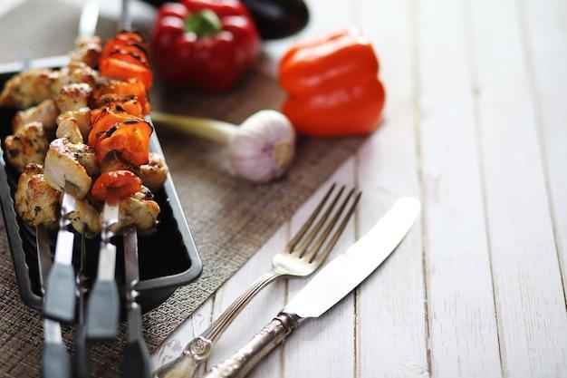 Kebab gotowany na metalowych szaszłykach z warzywami podawany na białym stole