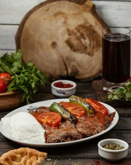 Kebab iskender przyozdobiony sosem pomidorowym, pieprzem, podawany z jogurtem