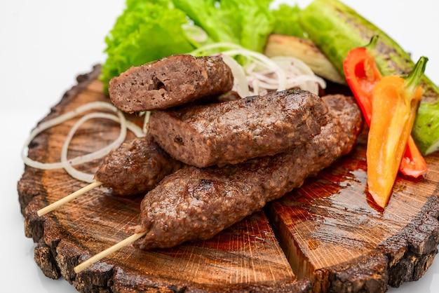 Kebab jagnięcy na desce serwującej z warzywami