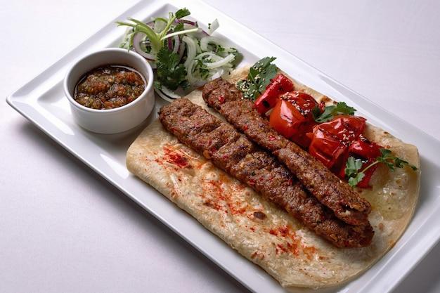 Kebab jagnięcy z pieczonymi pomidorami, cebulą i sosem, na białym talerzu, na białym tle
