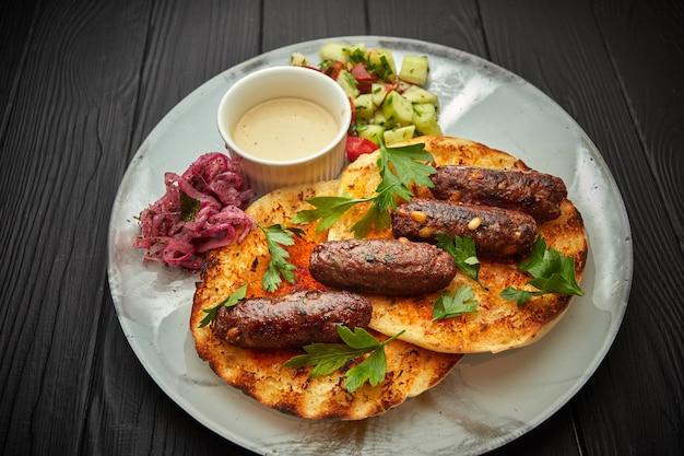 Kebab josper wołowy z orzeszkami pinii, pitą, sosem i warzywami, na czarnym tle