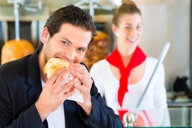 Kebab - klient i gorący doner ze świeżymi składnikami