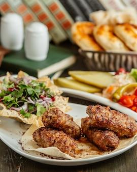 Kebab lula podany z siekaną cebulą i zieleniną