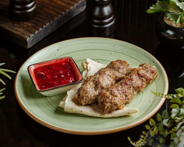 Kebab lula podawany z płaskimi chlebkami i sosem z granatów, cebuli i ziół