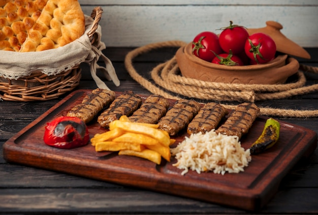 Kebab lula wołowy podawany z ryżem, smażonymi ziemniakami, grillowanym pomidorem i papryką
