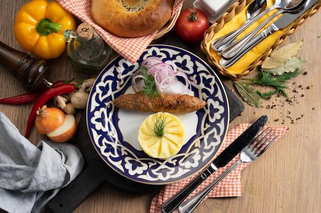 Kebab lula z puree ziemniaczanym, cebulą i koperkiem na talerzu z tradycyjnym uzbeckim