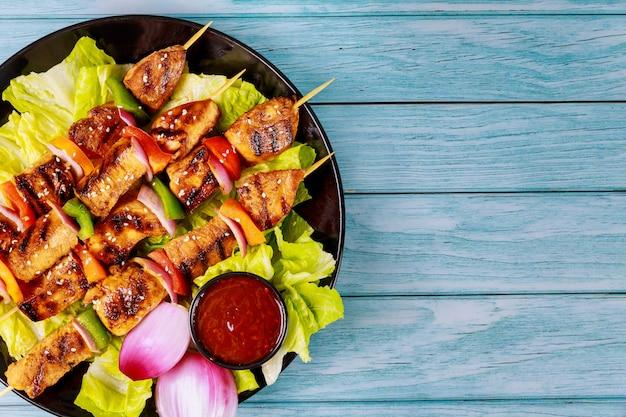 Kebab na drewnianym patyczku ze świeżą sałatką.