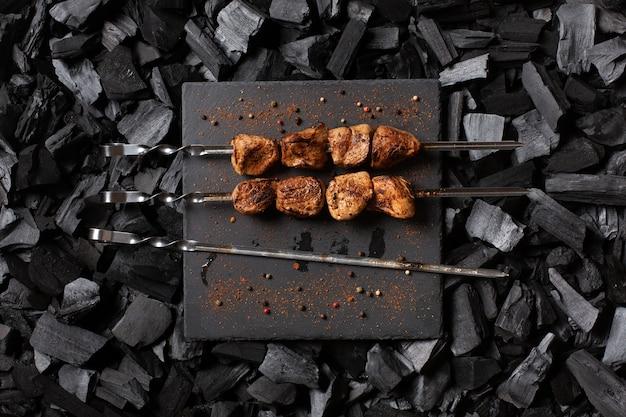 Kebab na szaszłykach. dwie porcje grillowanego mięsa na kamiennym talerzu i jedna pusta szpikulec.