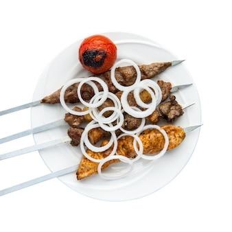 Kebab na szaszłykach w talerzu na białym tle. widok z góry. odosobniony. grill