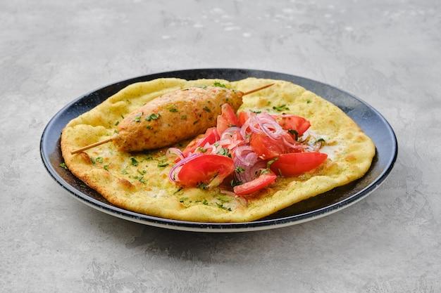 Kebab podany na tortilli z pomidorem i czerwoną cebulą