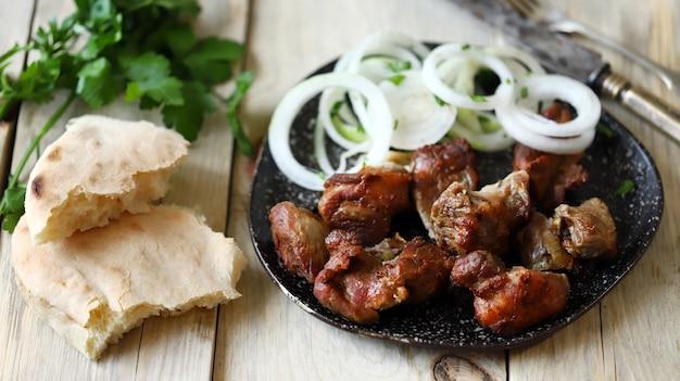 Kebab smażony z surową cebulą na talerzu.