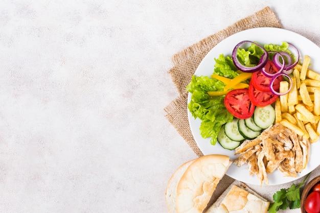 Kebab z gotowanego mięsa i warzyw na białym talerzu