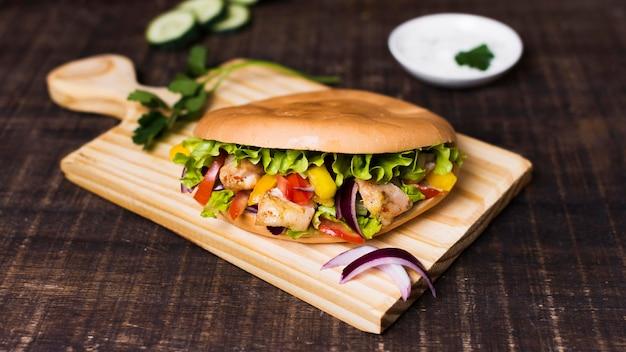 Kebab z gotowanego mięsa i warzyw na desce do krojenia