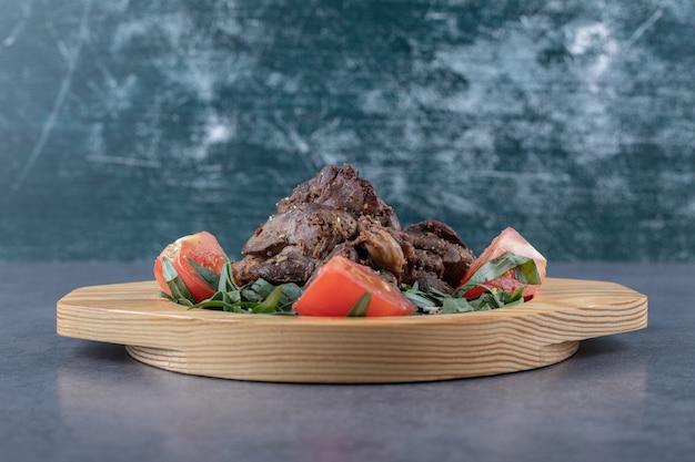 Kebab z grilla i plastry pomidora na drewnianym talerzu.