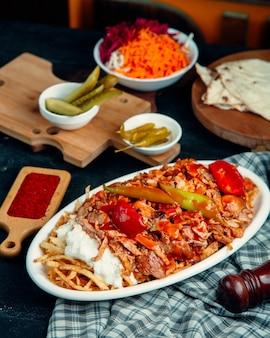 Kebab z jagnięciny przyozdobiony pomidorem i pieprzem, podawany z frytkami i jogurtem