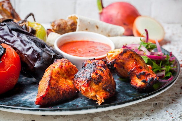 Kebab z kurczaka z sosem i smażonym bakłażanem i cebulą w okrągłym talerzu